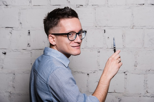 Young male hairdresser in glasses, posing with scissors, on gray brick wall background, back view