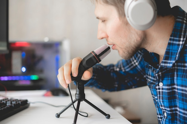 A young male handsome host recording podcast in the studio, streaming live