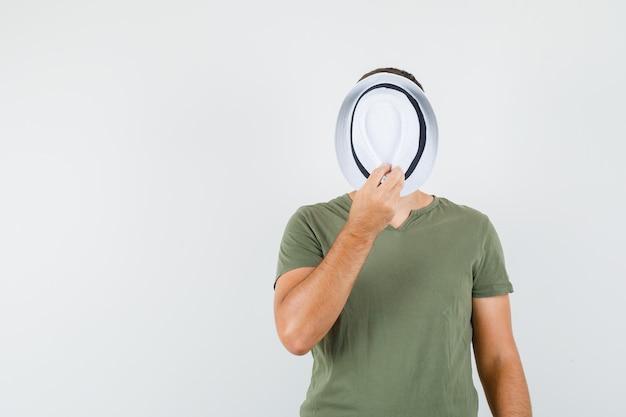 緑のtシャツ、正面図で帽子の後ろに顔を隠す若い男性。
