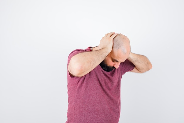Молодой мужчина прячет голову руками в розовой футболке.