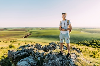 Young male hiker with backpack and binocular exploring green landscape