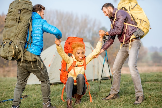 Young male hikers helping woman to get up staning with colorful backpacks on the green lawn near the camping place