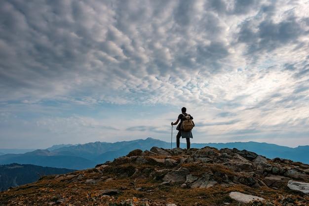 秋の山の若い男性のヒップスター