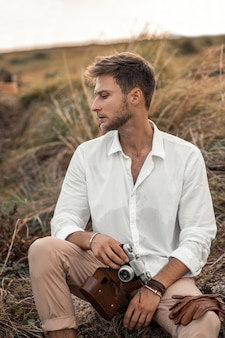 Young male hipster in a white shirt with old camera in his hands posing in the nature. explore unknown and look cool in strange scenery.