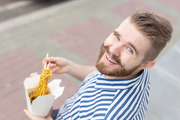 Young male hipster with a mustache and beard is eating chinese noodles with wooden chopsticks from a
