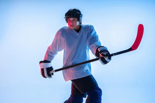 Giovane giocatore di hockey maschio con il bastone sulla parete blu alla luce al neon