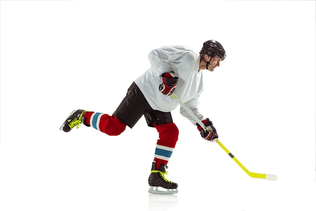 Young male hockey player with the stick on ice court and white background.