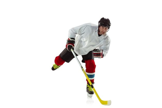 Giovane giocatore di hockey maschio con il bastone sul campo da ghiaccio e sfondo bianco.