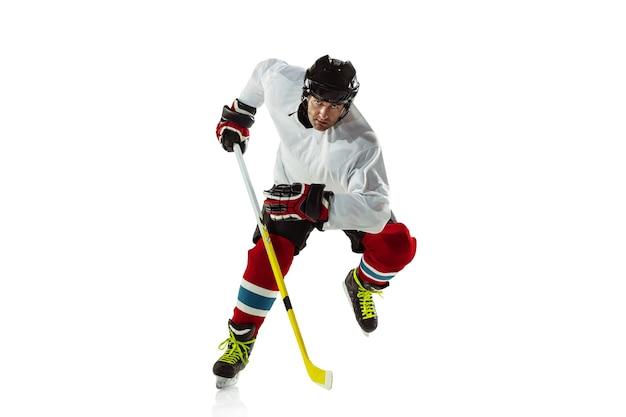 Giovane giocatore di hockey maschio con il bastone sul campo da ghiaccio e muro bianco. sportivo che indossa l'attrezzatura e il casco che si esercita nell'azione.