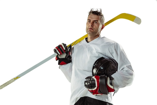 Giovane giocatore di hockey maschio con il bastone sul campo da ghiaccio e muro bianco