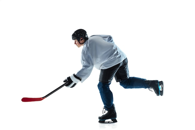 Young male hockey player with the stick on ice court and white wall