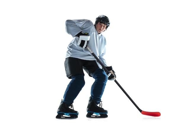 Giovane giocatore di hockey maschio con il bastone sul campo da ghiaccio