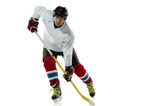 アイスコートと白い背景の上の棒を持つ若い男性のホッケー選手。