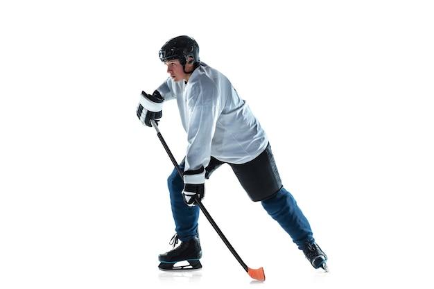 Молодой хоккеист мужского пола с клюшкой на ледовой площадке и белой стене
