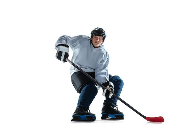 アイスコートと白い壁に棒で若い男性のホッケー選手