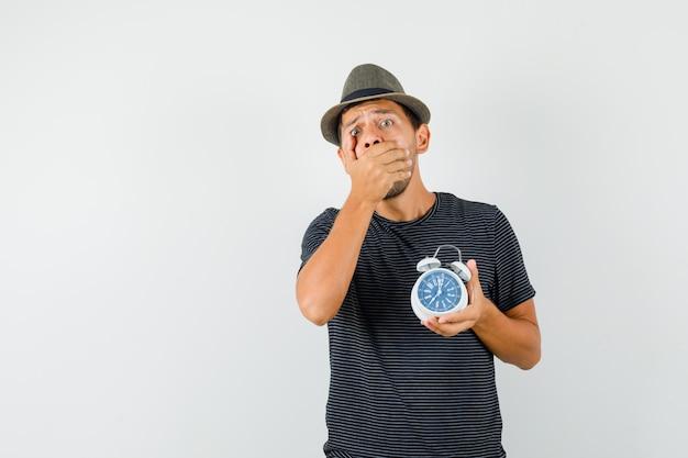 Молодой мужчина держит будильник в шляпе футболки и выглядит обеспокоенным