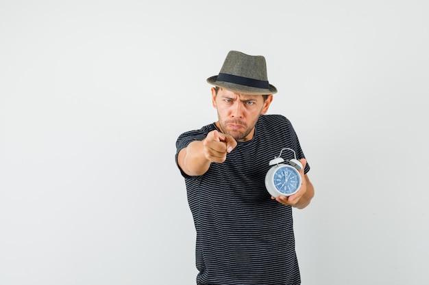 Молодой мужчина держит будильник, указывая на камеру в футболке и нервно смотрит