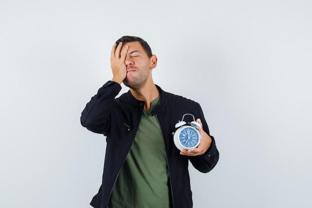 Tシャツ、ジャケット、忘れっぽい顔に手で目覚まし時計を保持している若い男性。正面図。