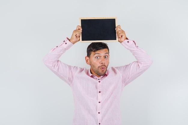 シャツの正面図で彼の頭の上に黒板を保持している若い男性。
