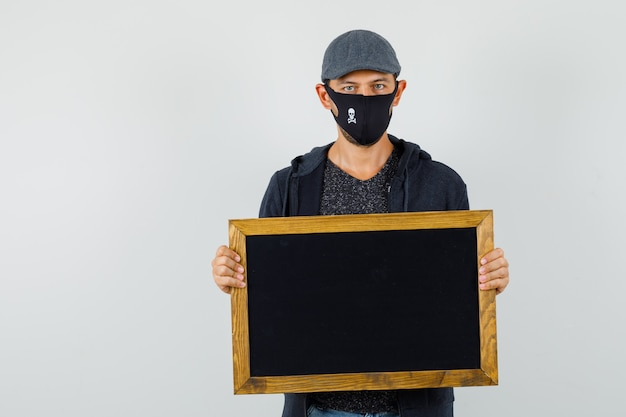 Tシャツ、ジャケット、キャップ、マスク、正面図で黒板を保持している若い男性。