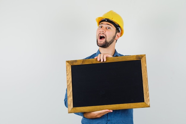 Young male holding blackboard in shirt, helmet and looking optimistic , front view.