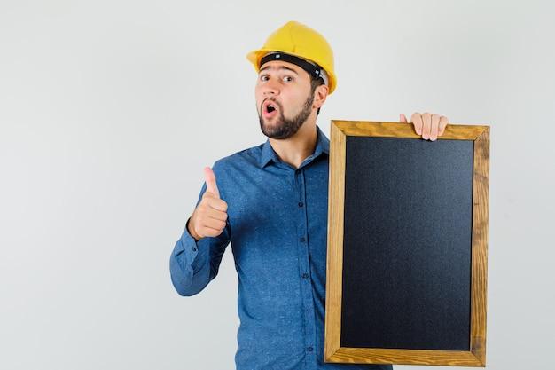 黒板を持って、シャツ、ヘルメットで親指を見せて、幸せそうに見える若い男性。正面図。