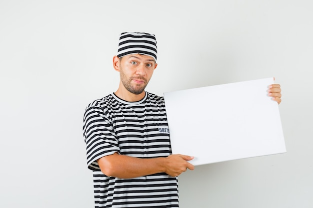 Молодой мужчина держит чистый холст в полосатой футболке и выглядит оптимистично