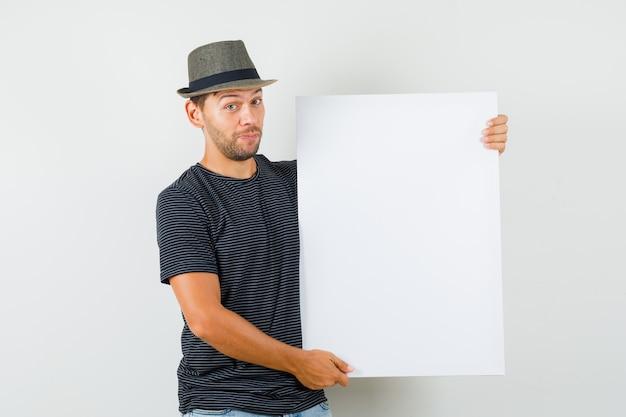 Молодой мужчина держит чистый холст в футболке и джинсовой шляпе и выглядит уверенно