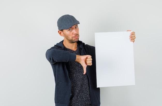 空白のキャンバスを保持している若い男性、tシャツ、ジャケット、キャップの正面図で親指を下に示しています。