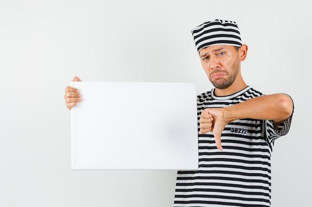 Giovane maschio che tiene tela bianca che mostra il pollice giù in cappello della maglietta a strisce e che sembra triste