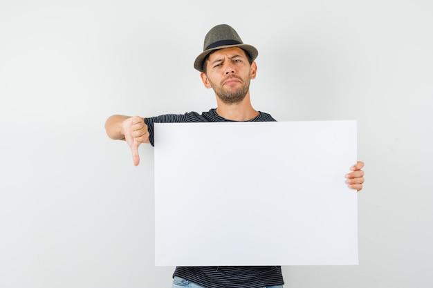 Giovane maschio che tiene tela di canapa in bianco che mostra il pollice giù in cappello dei jeans della maglietta