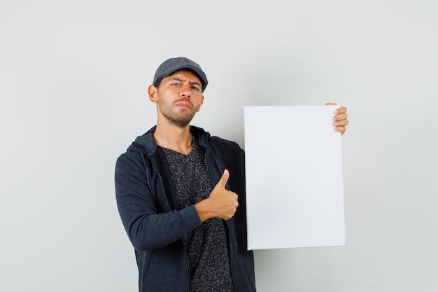 空白のキャンバスを保持し、tシャツ、ジャケット、キャップで親指を表示し、自信を持って見える若い男性。正面図。