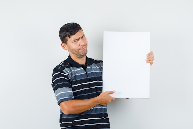 Young male holding blank poster in t-shirt , front view.