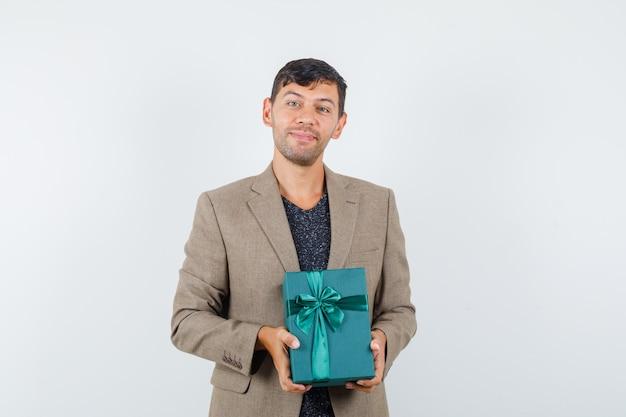 Contenitore di regalo blu della tenuta del giovane maschio in rivestimento marrone grigiastro e che sembra felice. vista frontale.