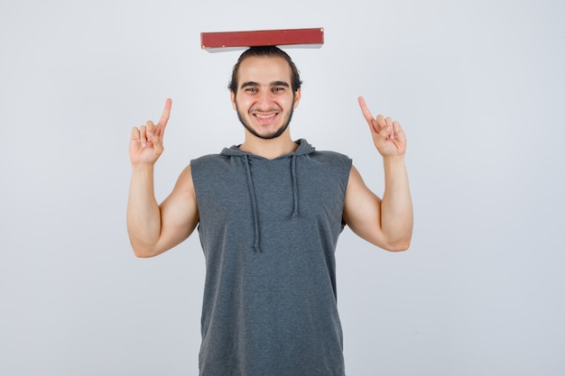 Young male holding book on head while pointing up in sleeveless hoodie and looking joyful. front view.