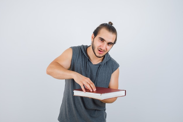 Young male holding book in sleeveless hoodie and looking confident , front view.