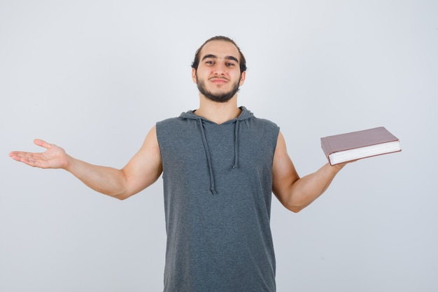 Young male holding book while making scales gesture in sleeveless hoodie and looking confident. front view.