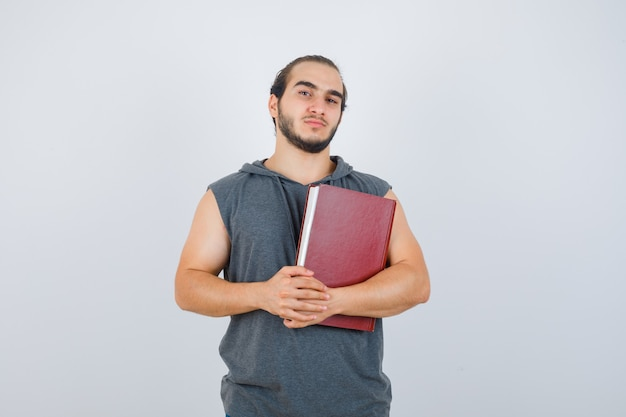 Young male holding book while posing in sleeveless hoodie and looking confident. front view.
