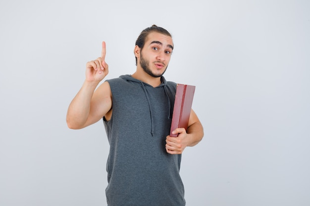 Young male holding book while showing pointing up in sleeveless hoodie and looking confident , front view.