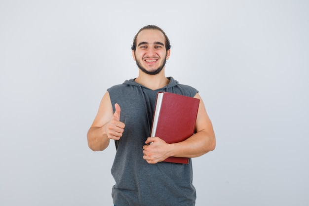 Young male holding book while showing thumb up in sleeveless hoodie and looking happy , front view.