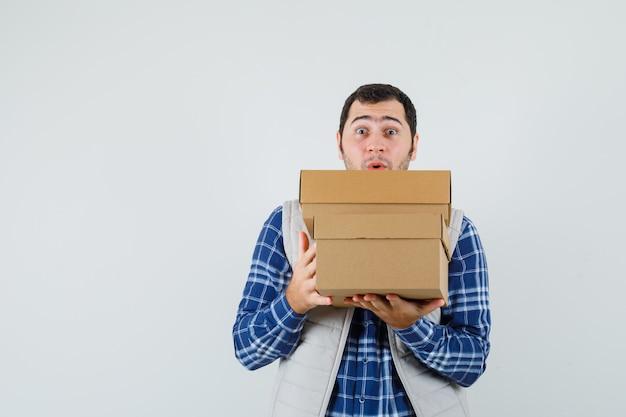 젊은 남성 셔츠, 재킷에 상자를 들고 놀 찾고, 전면보기.