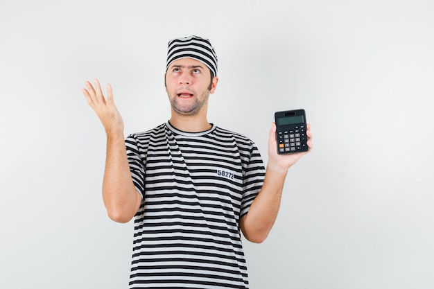 Young male holding calculator in t-shirt, hat and looking hesitant. front view.