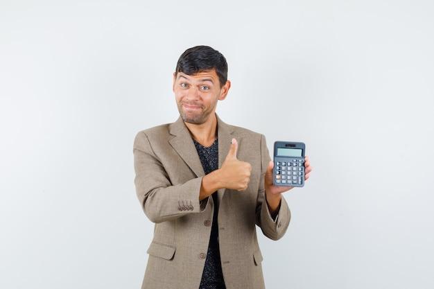 灰色がかった茶色のジャケット、黒いシャツ、嬉しそうに見える、正面図で親指を表示しながら電卓を保持している若い男性。