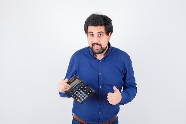 ロイヤルブルーのシャツの正面図で親指を表示しながら電卓を保持している若い男性。