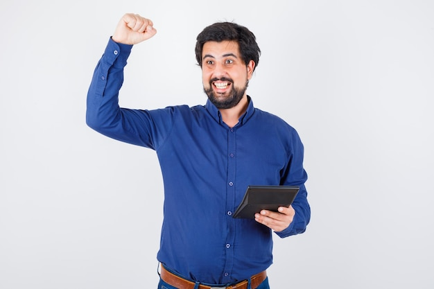 Young male holding calculator while showing winner gesture in royal blue shirt front view.
