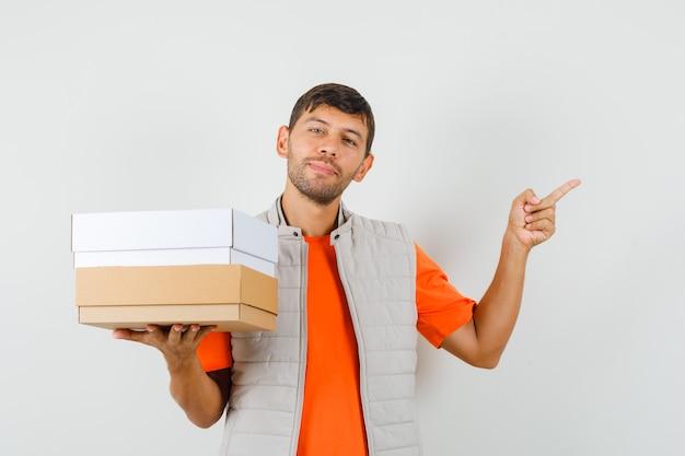 Молодой мужчина держит картонные коробки, указывая в сторону в футболке, куртке и выглядит весело, вид спереди.
