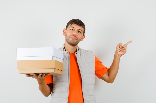 Young male holding cardboard boxes, pointing away in t-shirt, jacket and looking cheery , front view.