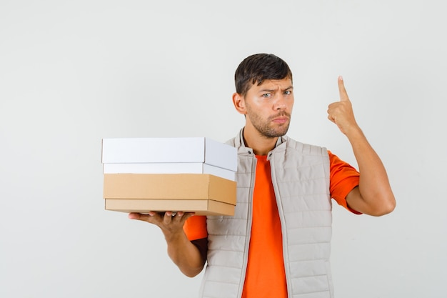 Young male holding cardboard boxes, pointing up in t-shirt, jacket , front view.