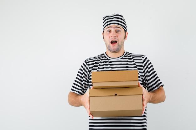 Giovane maschio che tiene le scatole di cartone in maglietta, cappello e che sembra allegra. vista frontale.