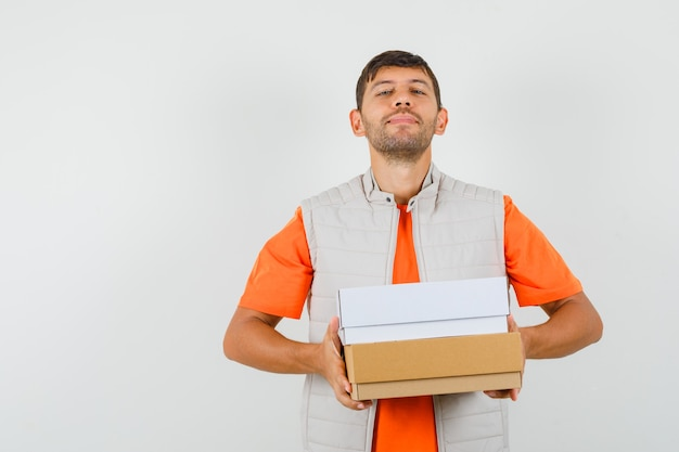 Young male holding cardboard boxes in t-shirt, jacket and looking confident. front view.